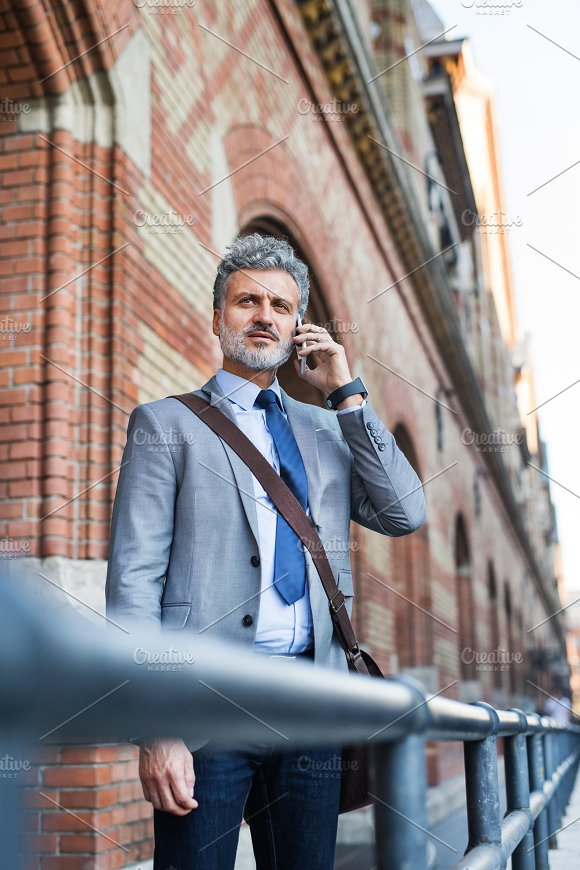 Mature businessman with smartphone in a city. in Graphics