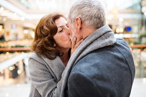 Senior couple doing Christmas shopping, kissing.