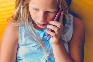 The girl listens to what she is told by phone