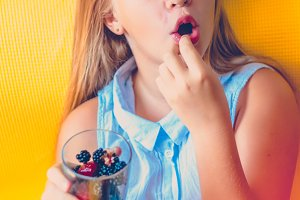 Girl with blue eyes eating berries