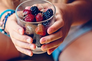 Girl holding a glass with blackberries and strawberries