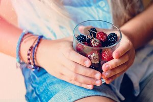 Strawberries and blackberries. Children's hands