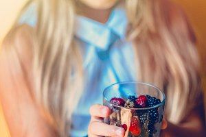 Girl offers a glass with berries. On hand bracelets