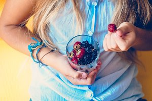 A glass in the hands of a girl. Berries for health