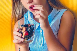 Girl eats blackberries and strawberries