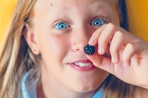 Yellow background. Blue eyes of a girl. Blackberry instead of nose