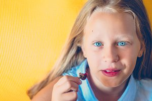 Blue eyes of a girl. Ate strawberries