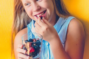 Smile at the child. Vitamins for children. Berries