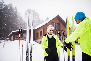 Senior couple getting ready for cross-country skiing.