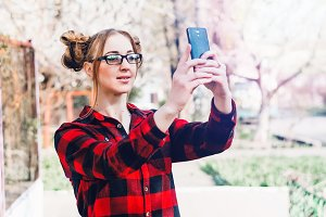 Girl posing on camera phone. holds the phone in his hands. glasses on the eyes