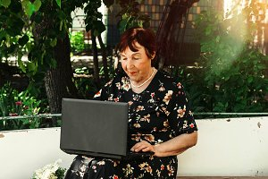 the grandmother looks at the laptop monitor. sits on the street