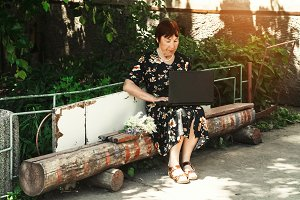 grandmother sits on a bench for a laptop.