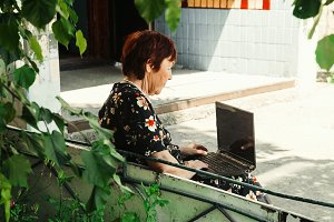 An elderly woman is sitting at the laptop. modern grandmother