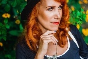 beautiful woman. portrait. Red hair. Hat on the head.