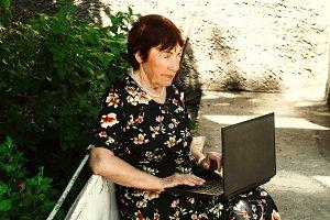 grandma behind laptop. advanced elderly woman. communication on the Internet
