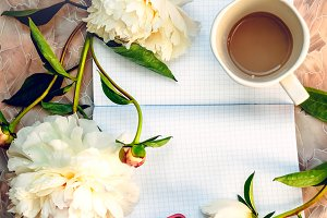 Phone on the desktop. Hot coffee for the morning. Peonies