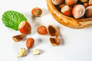 Hazelnut nuts in a wooden bowl on a white wooden table. Superfood.