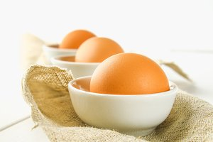 Raw brown chicken eggs in glass bowls on a white wooden table. Ingredients for cooking.