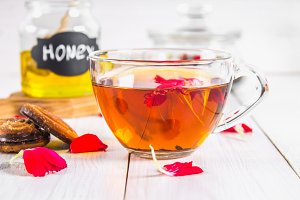 A cup of tea, biscuits, in the background of a can of honey and a pot of black herbal floral tea on a white wooden table.