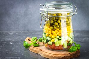 Healthy homemade salad in a jar with vegetables, cucumbers, tomatoes, peas and corn - Healthy diet, detox, pure food or vegetarian concept.