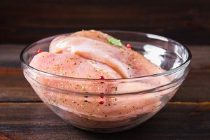 Raw chicken fillet in a glass bowl on the background of a wooden table. Meat ingredients for cooking.