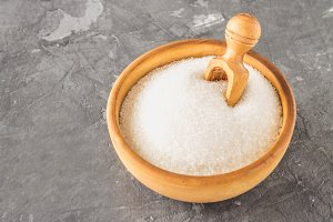 White sugar sugar in a wooden plate with a dustpan on a dark background.