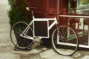 the bike is on the street. a blank black banner. decor and design.