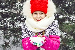 the child enjoys the snow. holds snow in his hands. portrait of a girl on the street. snowing