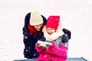 Mom and daughter. happy together. viewing on the screen. technologies. walk in winter. snow