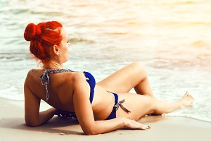 Rest at the sea. Beautiful woman with a red hair color in a bathing suit. travel and resort
