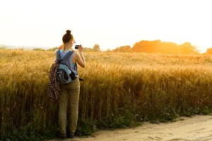 Young girl takes pictures of the sunset on a summer evening