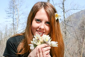 Beautiful young girl is sniffing a bouquet of flowers. White flowers. Brown-haired woman with flowers.