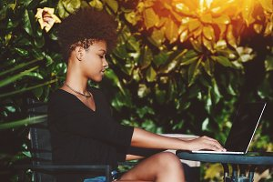 Black girl with netbook in the park