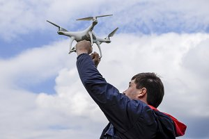 A man with a quadrocopter in his arms raised to the sky. A white drone is being prepared for the flight.