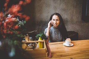 beautiful young brunette girl talking on mobile phone at wooden table near window and drinking coffee in cafe decorated with Christmas decor. Dressed in a gray knitted wool sweater