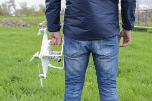 A man with a quadrocopter in his hands. White kvadrokopter prepare for flight