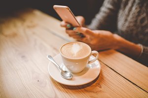 hands close-up of a beautiful young girl uses,types text on a mobile phone at a wooden table near a window and drinks coffee in a cafe decorated with Christmas decor. Dressed in a gray knitted sweater