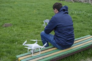 A man with a remote control quadroopter in his hands is sitting on a bench. White quadroopter prepare for flight.