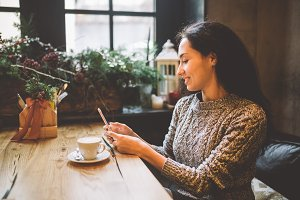 beautiful young girl uses, types text on a mobile phone at a wooden table near the window and drinks coffee in a cafe decorated with Christmas decor. Dressed in a gray knitted wool sweater