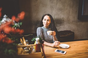 beautiful young girl drinks coffee from a white cup, next to her cell phone in a cafe decorated with Christmas decor. Dressed in a gray knitted wool sweater