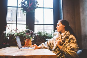 beautiful young girl uses laptop technology, types text looking at the monitor in a cafe by the window at wooden table, in winter decorated with Christmas decor.Dressed in a gray knitted wool sweater