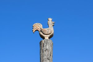 Figurine of a rooster on a tree stump on a background of blue sky. Figures of animals made of wood. Woodcarving