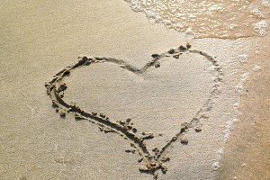 Heart drawn on the beach sand