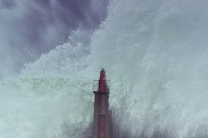 Stormy wave over old lighthouse