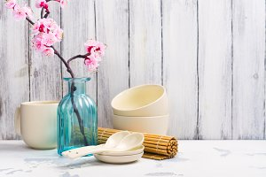 Japanese utensils, dinnerware, chopsticks and branch of blooming sakura on white asian background