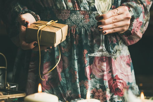 Holiday Stock Photos - Woman holding glass of champaigne and gift box, Christmas eve