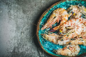 Raw uncooked tiger prawns on chipped ice, grey background