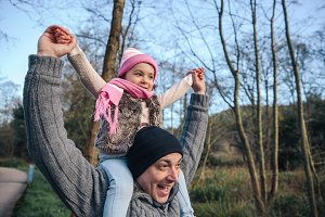Man giving piggyback ride to happy girl outdoors