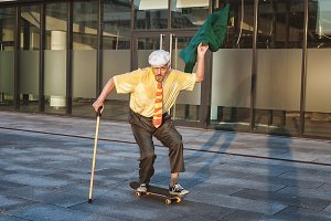 Old man is riding a skateboard.