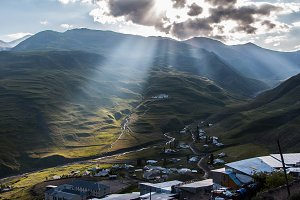 Mountain Village with Sun Rays